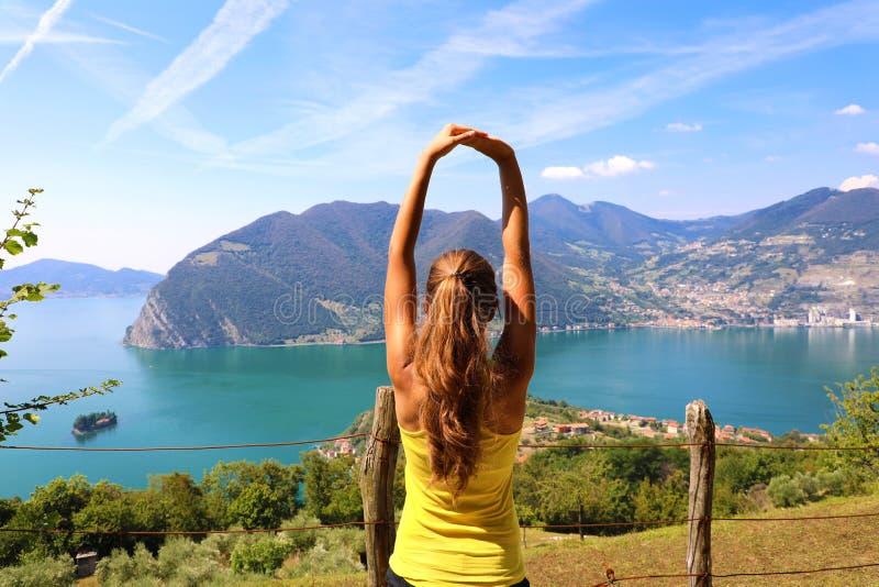 Upphetsad attraktiv ung kvinna i sportswearen som sträcker tycka om det sjöIseo landskapet i morgonen, norr Italien Gladlynt mood royaltyfri bild