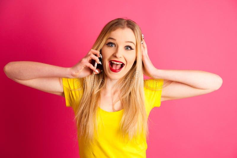 Upphetsad blond tonårs- flicka som talar på den smarta telefonen över rosa färgbac royaltyfri foto
