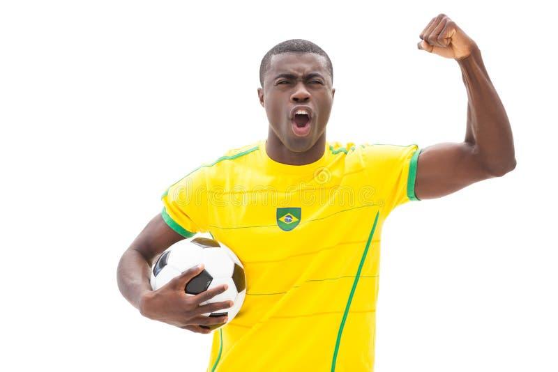 Upphetsad brasiliansk boll för fotbollsfanbifallinnehav fotografering för bildbyråer