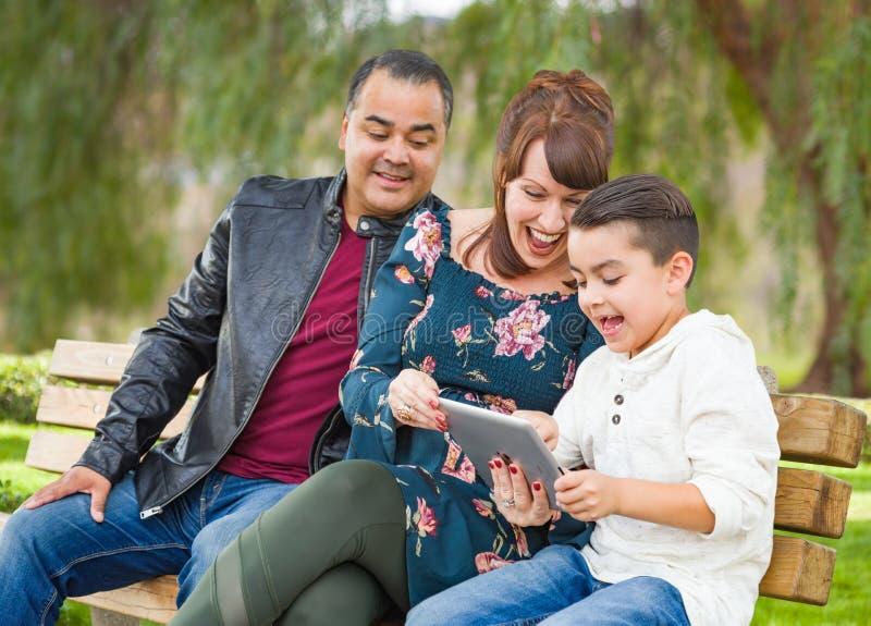 Upphetsad Caucasian moder och latinamerikansk fader Using Computer Tablet med sonen för blandat lopp utomhus royaltyfri fotografi