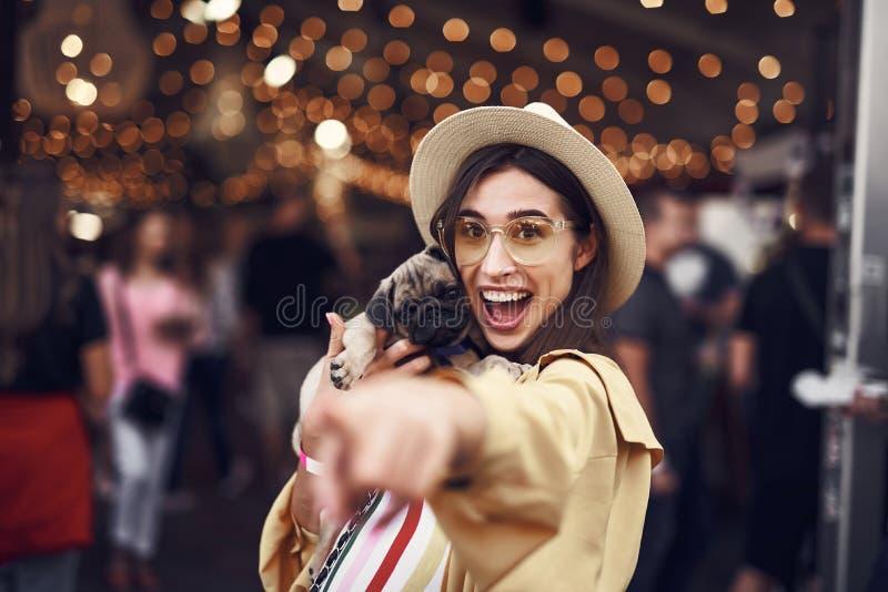 Upphetsad dam som pekar till kameran, medan rymma hennes gulliga valp royaltyfria bilder