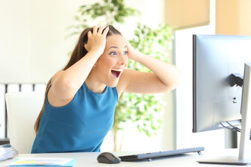 Upphetsad entreprenör som kontrollerar datorinnehållet royaltyfri fotografi