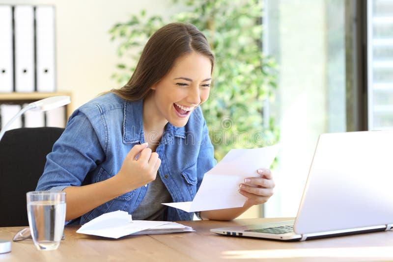 Upphetsad entreprenörflicka som läser ett brev royaltyfri foto