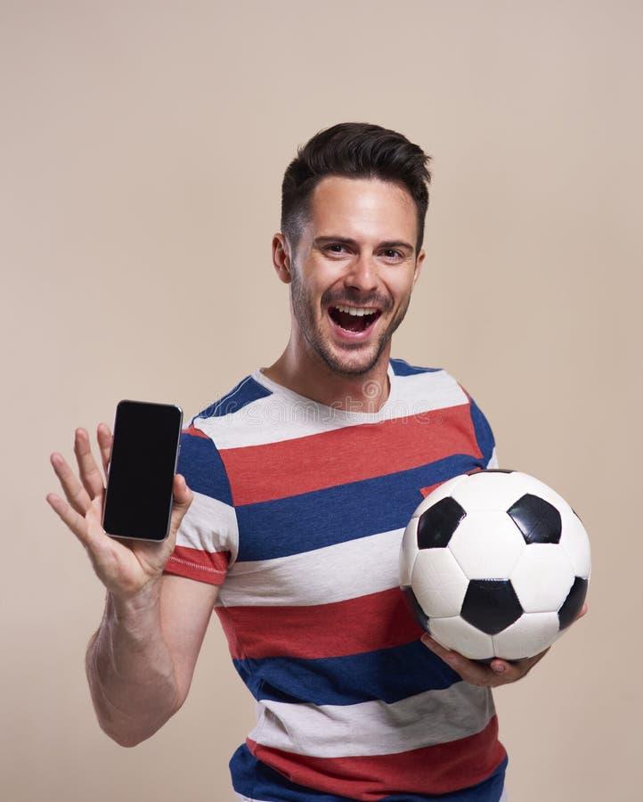 Upphetsad fan som rymmer fotbollbollen och visar mobiltelefonen fotografering för bildbyråer