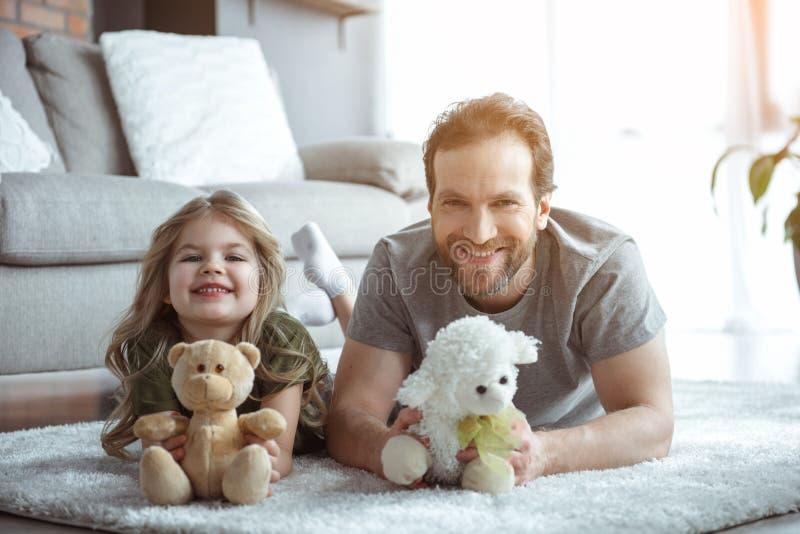 Upphetsad farsa och flicka som spelar med nallebjörnen royaltyfri bild