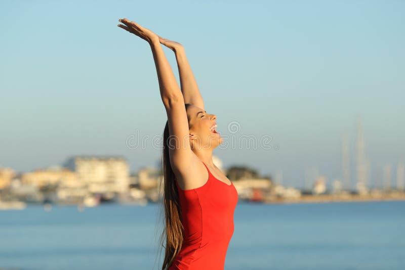 Upphetsad flicka i röd fira semester på stranden royaltyfri foto