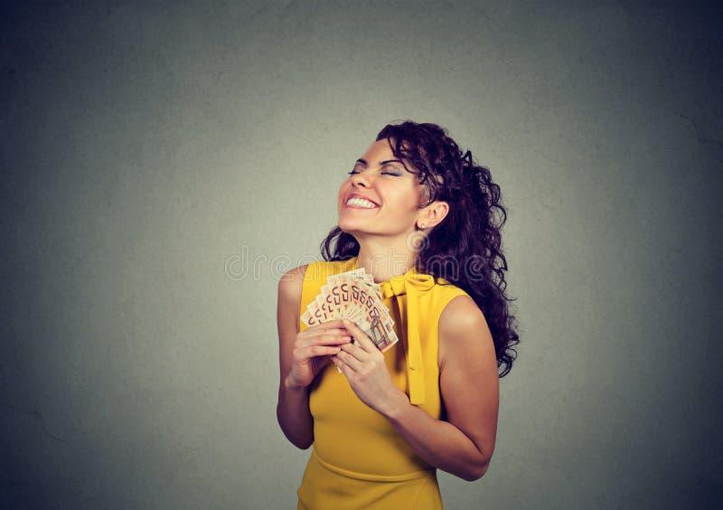 Upphetsad flicka med högen av pengar royaltyfri fotografi