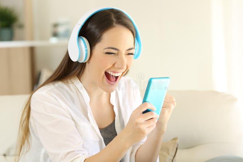 Upphetsad flicka som finner online-lyssna för erbjudanden till musik arkivfoton