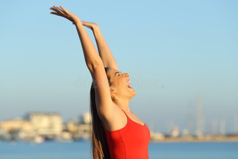 Upphetsad flicka som firar frihet på stranden royaltyfri foto