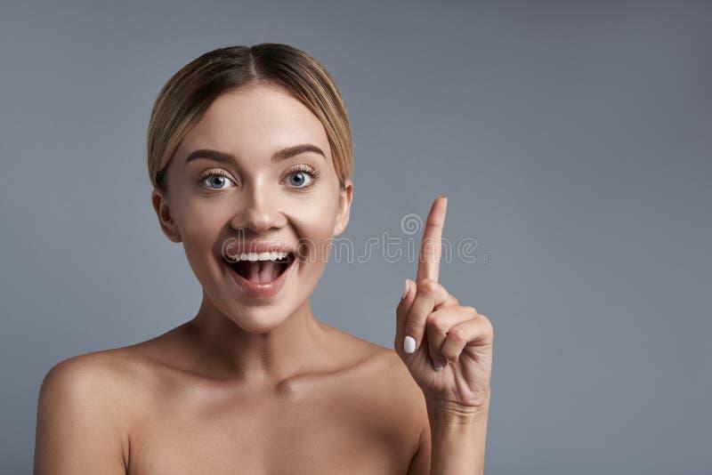 Upphetsad flicka som pekar upp hennes finger och ser lycklig arkivfoton