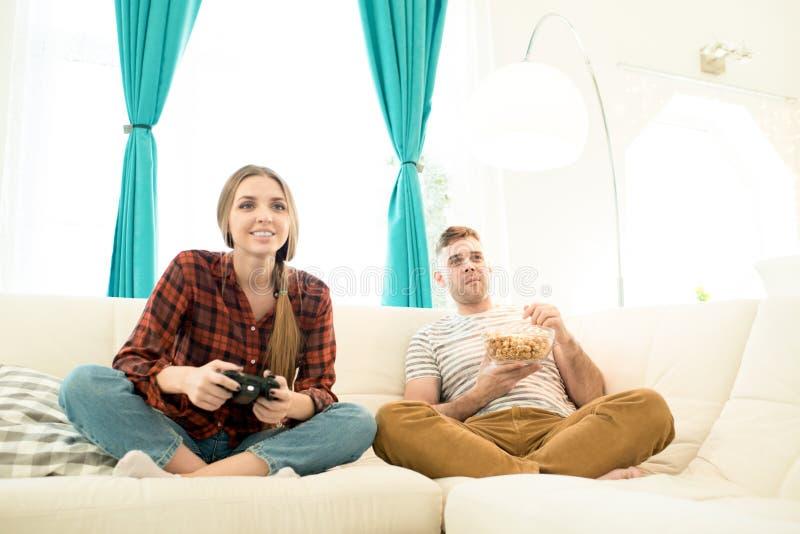 Upphetsad flicka som spelar videospelet medan pojkvän som äter popcorn royaltyfria foton
