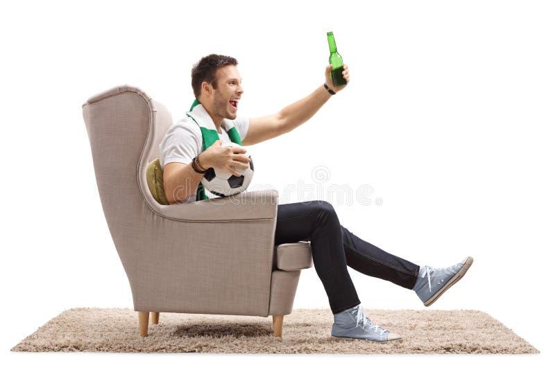 Upphetsad fotbollfan med en halsduk och en flaska av öl fotografering för bildbyråer