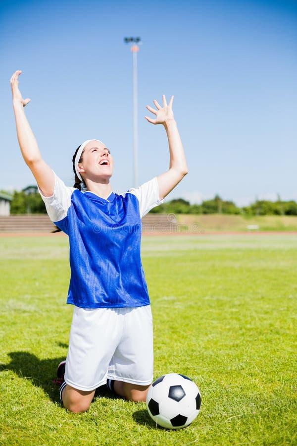 Upphetsad fotbollspelare som poserar efter seger arkivbild