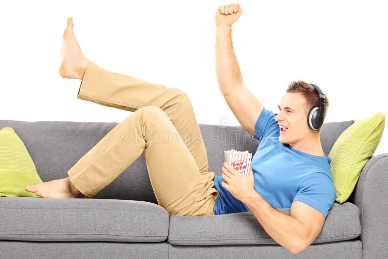 Upphetsad grabb som ligger på en modern soffa och en lyssnande musik fotografering för bildbyråer