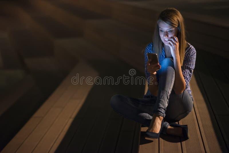 Upphetsad härlig flicka som mottar ett smsmeddelande med goda nyheter i en mobiltelefon utanför royaltyfri bild