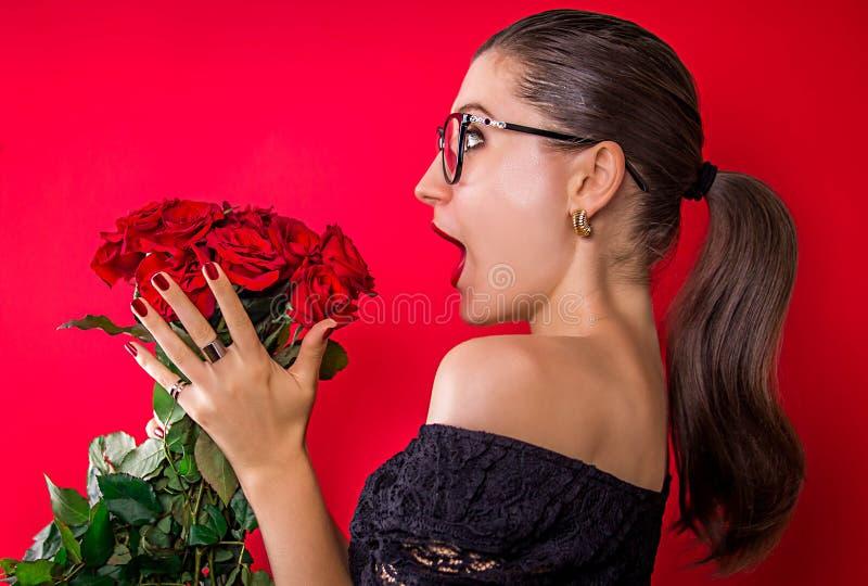Upphetsad härlig kvinna att få rosor arkivbild