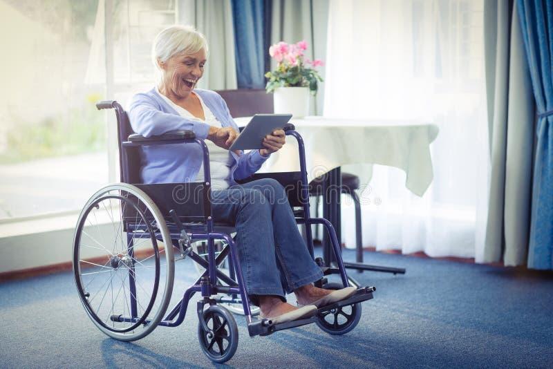 Upphetsad hög kvinna på rullstolen genom att använda den digitala minnestavlan royaltyfri bild