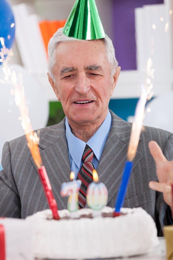 Upphetsad hög man som ser hans födelsedagkaka royaltyfria bilder