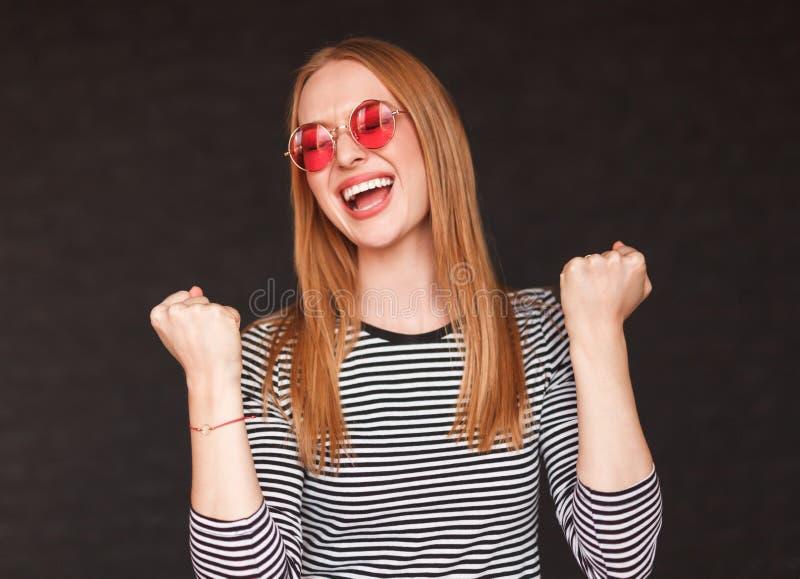 Upphetsad hipsterkvinna med nävar upp royaltyfria bilder