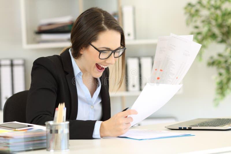 Upphetsad kontorsarbetare som kontrollerar försäljningsrapporter royaltyfria foton