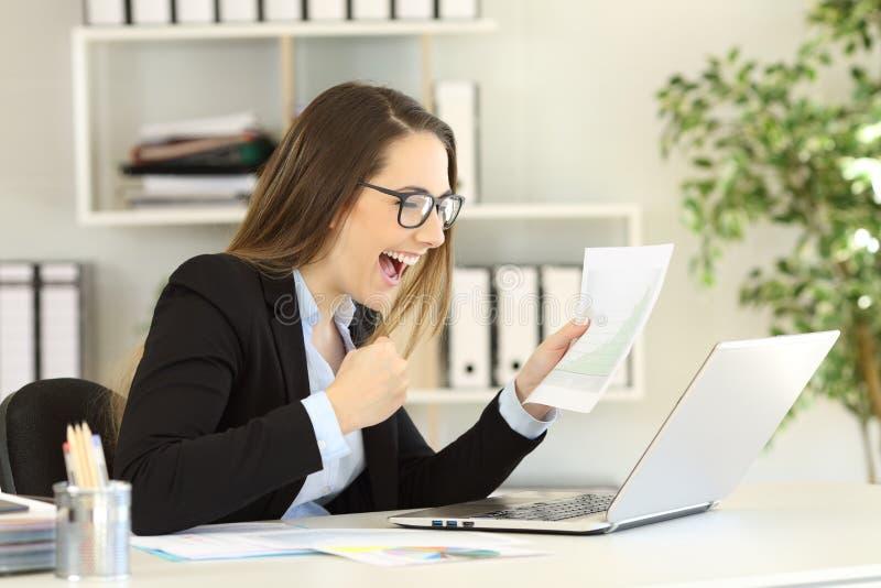 Upphetsad kontorsarbetare som kontrollerar förtjänstgrafen arkivbild