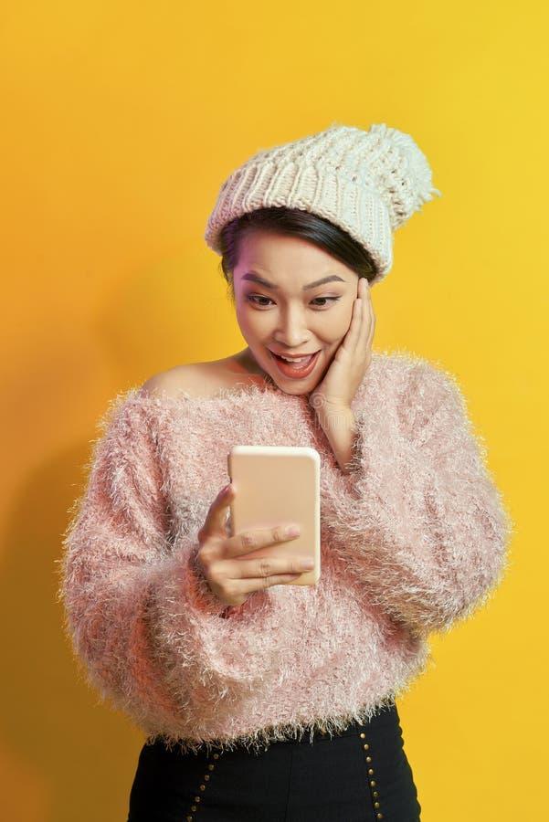 Upphetsad kort-haired kvinnainnehavsmartphone på orange bakgrund Inomhus foto av den underbara kvinnliga modellen med att posera  arkivbild