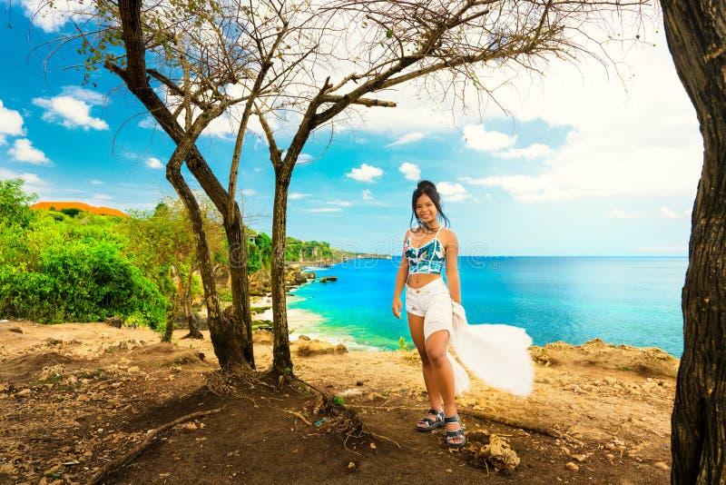 Upphetsad kvinna för handelsresande att tycka om förbluffa den tropiska stranden Pantai Bali för naturlandskap från överkant av b royaltyfri fotografi