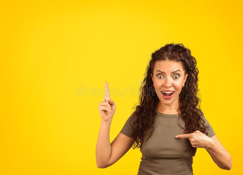 Upphetsad kvinna i överraskning som pekar på henne royaltyfria foton