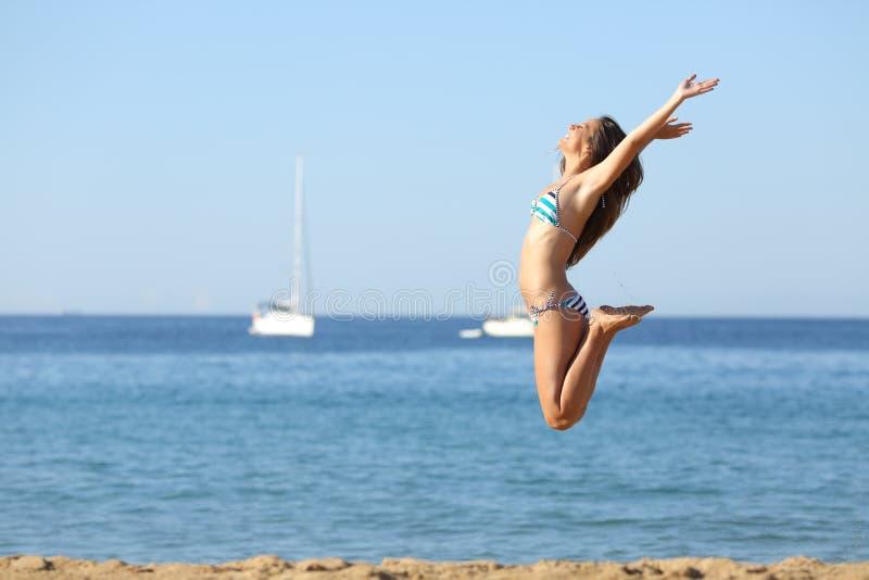 Upphetsad kvinna i bikinibanhoppning p? stranden arkivfoton