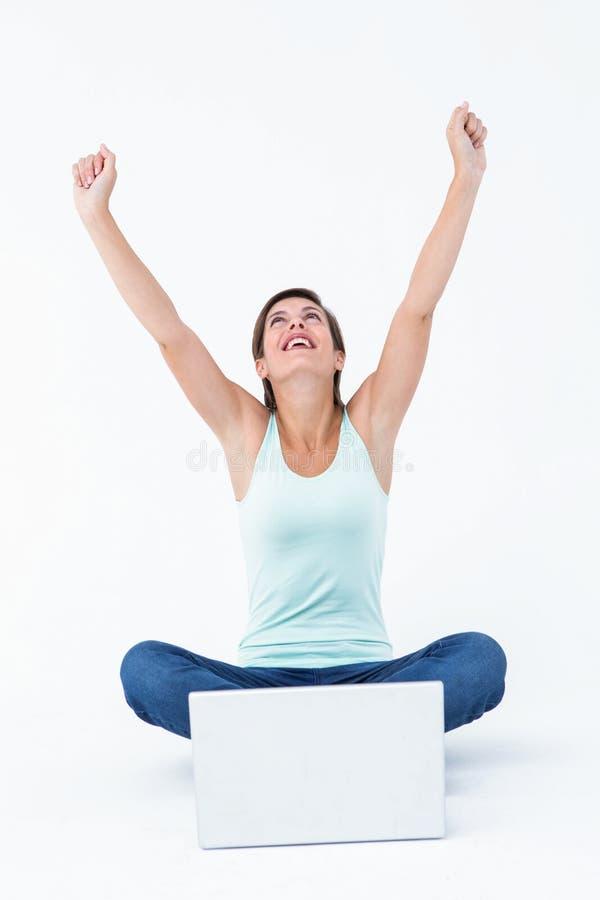 Upphetsad kvinna med bärbara datorn som lyfter henne armar fotografering för bildbyråer