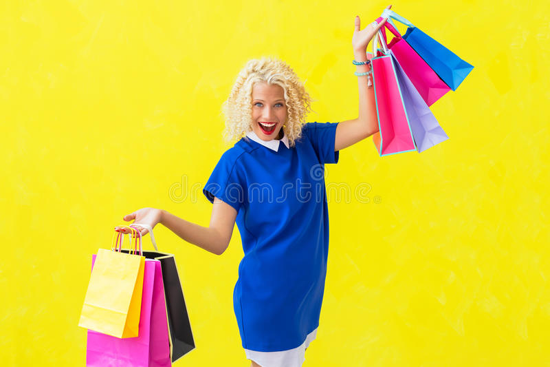 Upphetsad kvinna med shoppingpåsar royaltyfria bilder