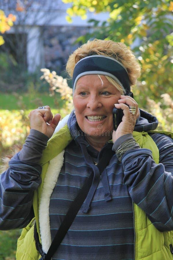 Upphetsad kvinna på mobiltelefonen royaltyfri foto
