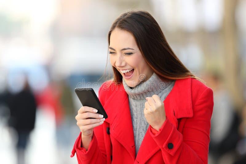 Upphetsad kvinna som använder en smart telefon i vinter arkivfoton