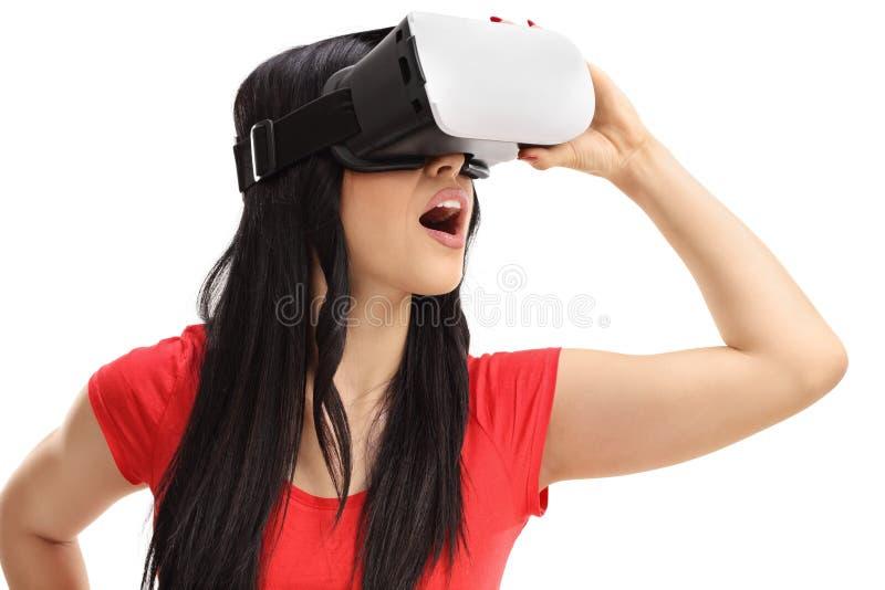 Upphetsad kvinna som använder en VR-hörlurar med mikrofon royaltyfri foto