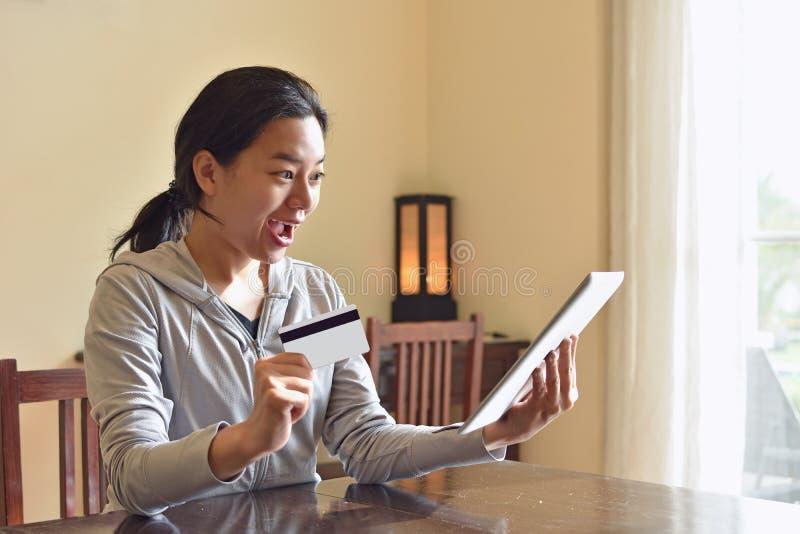 Upphetsad kvinna som direktanslutet hemma shoppar med minnestavlan royaltyfria bilder
