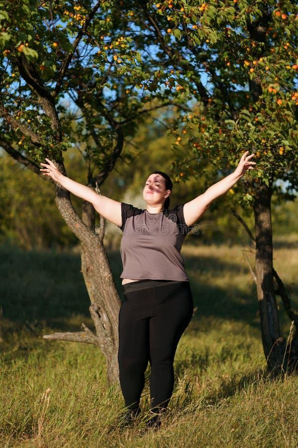 Upphetsad kvinna som firar framgång med armar upp arkivfoto