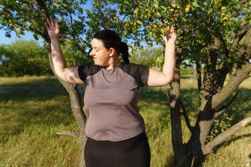 Upphetsad kvinna som firar framgång med armar upp royaltyfri foto