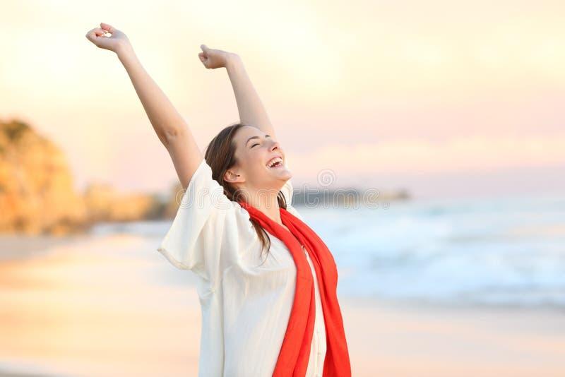 Upphetsad kvinna som firar solnedgången som lyfter armar royaltyfria foton