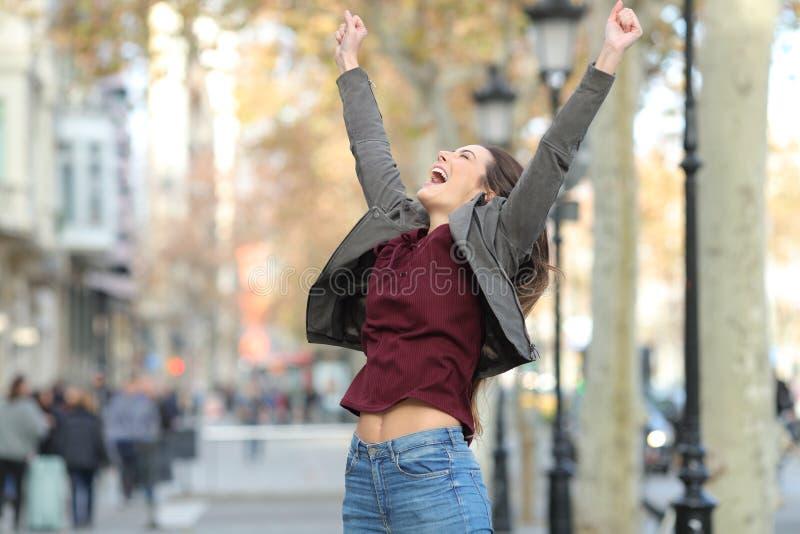 Upphetsad kvinna som hoppar i gatan royaltyfri bild
