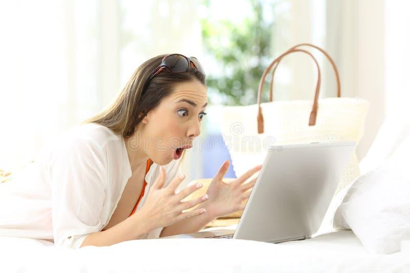 Upphetsad kvinna som läser online-innehållet på semestrar arkivfoton
