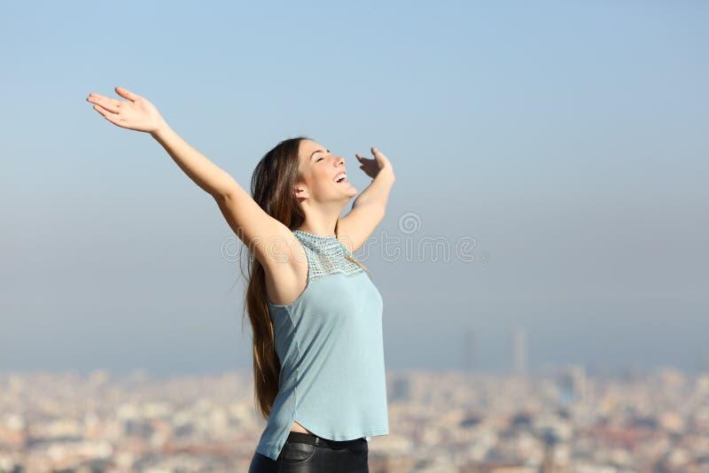 Upphetsad kvinna som lyfter armar som firar semester fotografering för bildbyråer