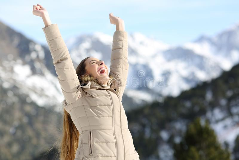 Upphetsad kvinna som lyfter armar i det snöig berget royaltyfri bild