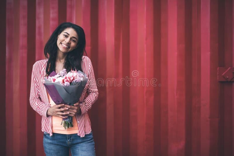 Upphetsad kvinna som rymmer älskvärda blommor och lyckligt ler royaltyfria foton