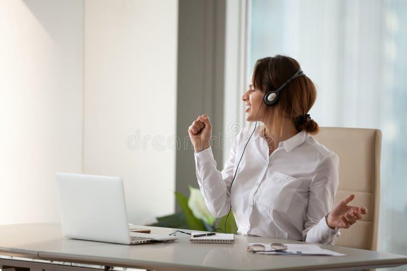 Upphetsad kvinnlig arbetare som i regeringsställning lyssnar till favorit- spår royaltyfri bild