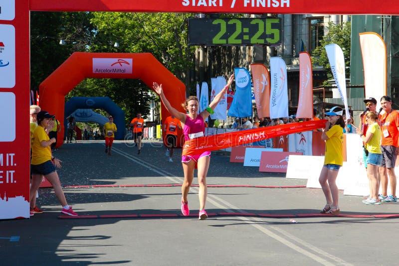 Upphetsad kvinnlig löpare som korsar finshlinen av en maraton arkivbild
