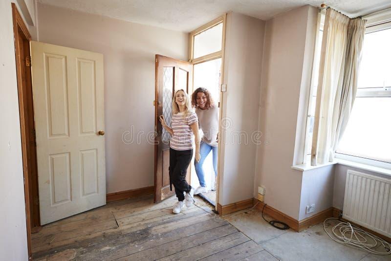 Upphetsad kvinnlig paröppning Front Door Of New Home royaltyfria bilder