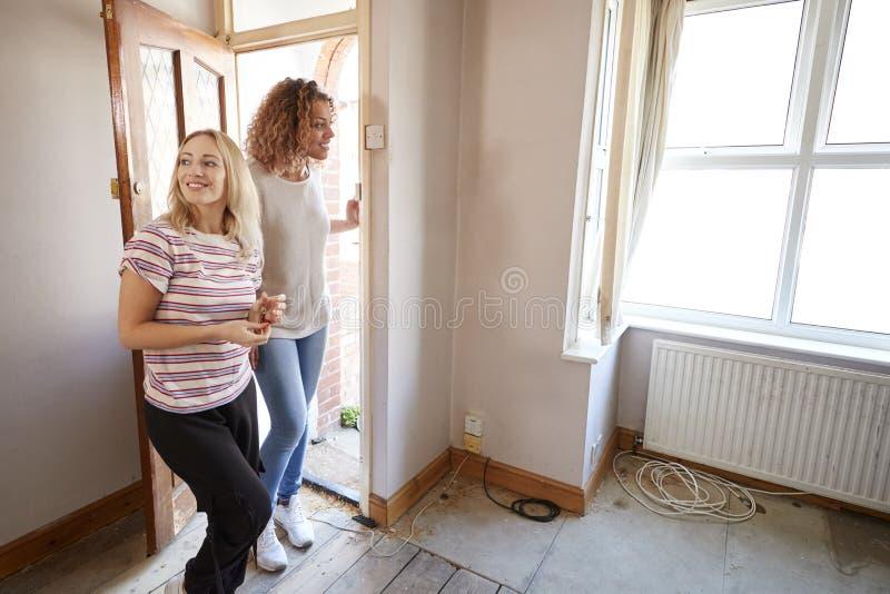 Upphetsad kvinnlig paröppning Front Door Of New Home arkivfoto