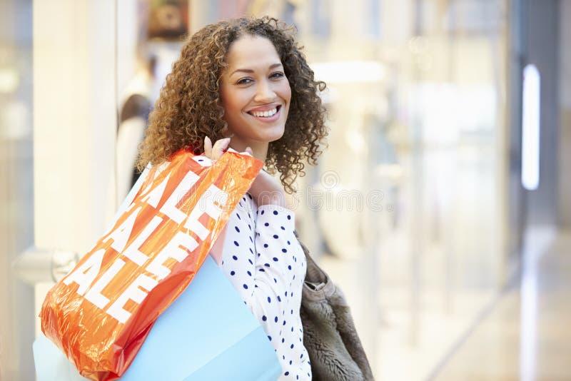 Upphetsad kvinnlig shoppare med Sale påsar i galleria arkivbild