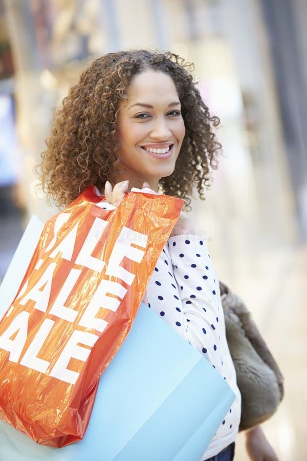 Upphetsad kvinnlig shoppare med Sale påsar i galleria royaltyfri bild