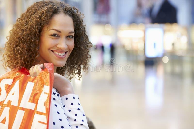 Upphetsad kvinnlig shoppare med Sale påsar i galleria arkivfoton